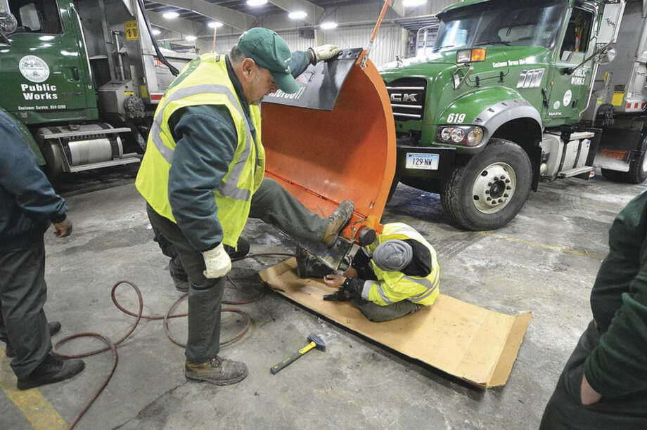 Hour Photo/Alex von Kleydorff Don Bradley and Paul Gasparo work on installing new plow blades on some of the Norwalk Public Works snow plows in advance of a major winter storm on Monday