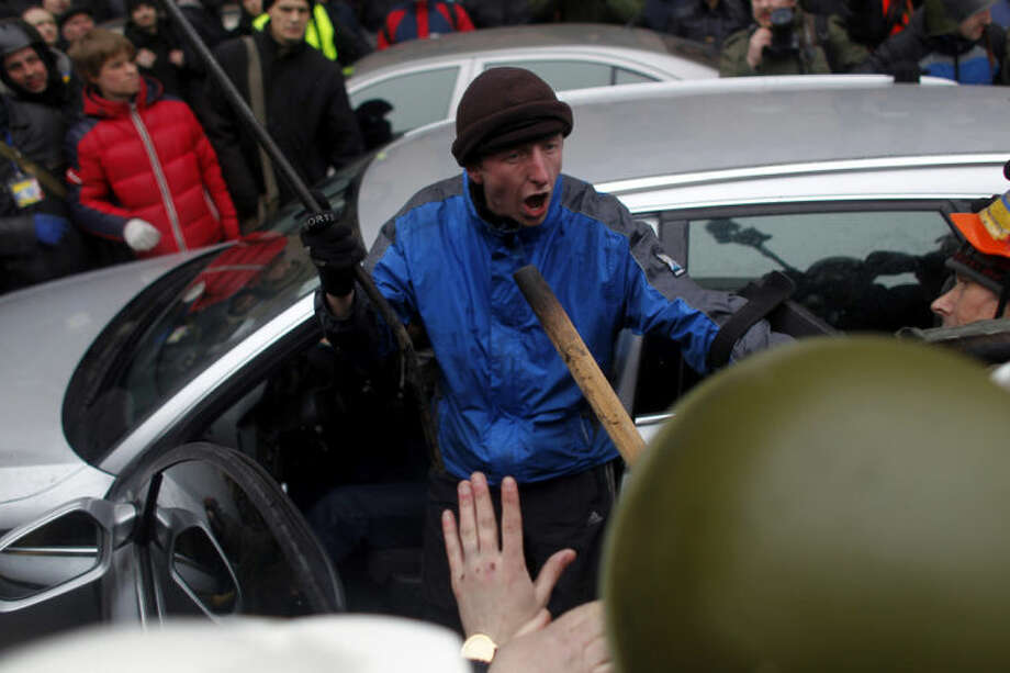 An anti-government protester tries to protect suspected supporters of Ukraine's embattled president Viktor Yanukovych from getting assaulted in Kiev, Ukraine, Saturday, Feb. 22, 2014. Fears that Ukraine could split in two mounted Saturday as regional lawmakers in the pro-Russian east questioned the authority of the national parliament. Protesters took control of Ukraine's capital and parliament sought to oust the president. (AP Photo/ Marko Drobnjakovic)