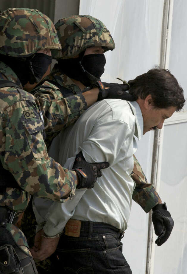 """Joaquin """"El Chapo"""" Guzman is escorted to a helicopter in handcuffs by Mexican navy marines at a navy hanger in Mexico City, Saturday, Feb. 22, 2014. A senior U.S. law enforcement official said Saturday, that Guzman, the head of Mexicoís Sinaloa Cartel, was captured alive overnight in the beach resort town of Mazatlan. Guzman faces multiple federal drug trafficking indictments in the U.S. and is on the Drug Enforcement Administrationís most-wanted list. (AP Photo/Dario Lopez-Mills)"""