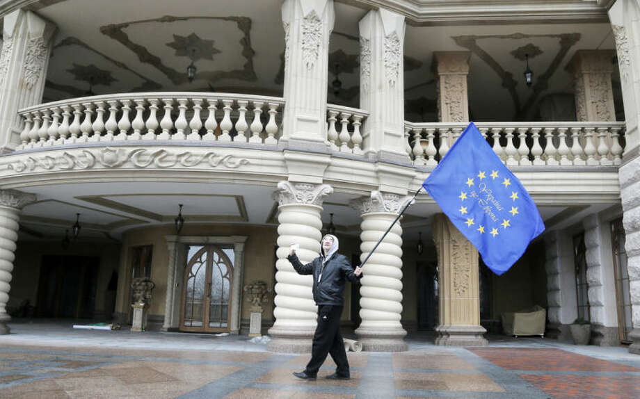 A protester waves an EU flag at the Ukrainian President Yanukovych country residence in Mezhyhirya, Kiev's region, Ukraine, Saturday, Feb, 22, 2014. Viktor Yanukovych is not in his official residence of Mezhyhirya, which is about 20 kilometres north of the capital. Ukrainian security and volunteers from among the Independence Square protesters have joined forces to protect the presidential countryside retreat from vandalism and looting. (AP Photo/Efrem Lukatsky)