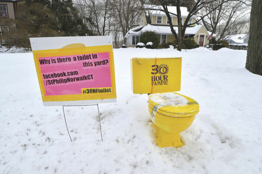 Hour Photo/Alex von KleydorffThis bright yellow toilet gets the attention of motorists along Dry Hill Rd in Norwalk.