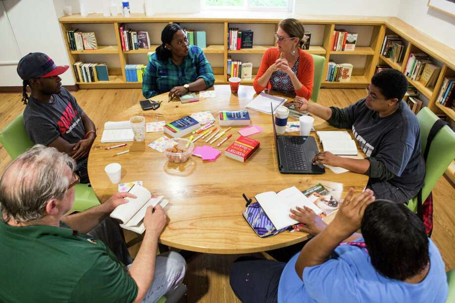 Stephanie Tsuru, top right, leads a book club meeting for people who are chronically homeless on Tuesday, April 26, 2016, in Houston. Shown clockwise from top center, Eboni Robinson, Surra Reagan, John Doberstein, Gene Scott and Washita McCoy. Photo: Brett Coomer, Houston Chronicle / © 2016 Houston Chronicle