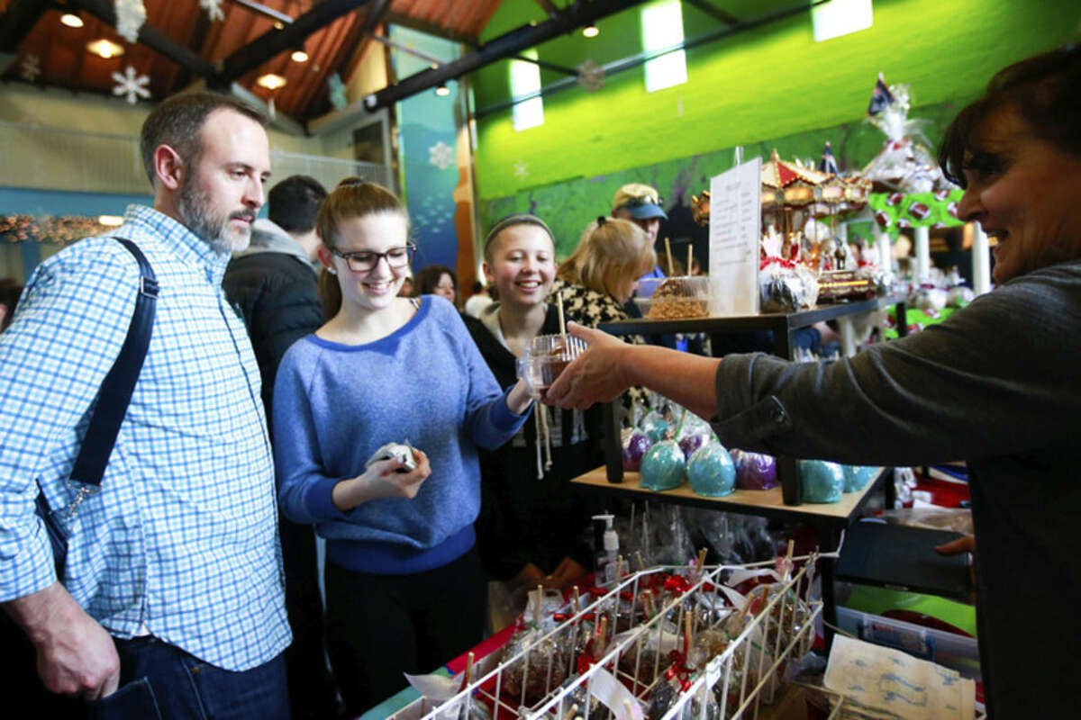 Hour photo/Chris Palermo Rob, Brooklyn and Kailyn Murphy gets a candy apple from Carousel Sweets by Ellie at the annual Chocolate Expo at the Maritime Aquarium in Norwalk Sunday.