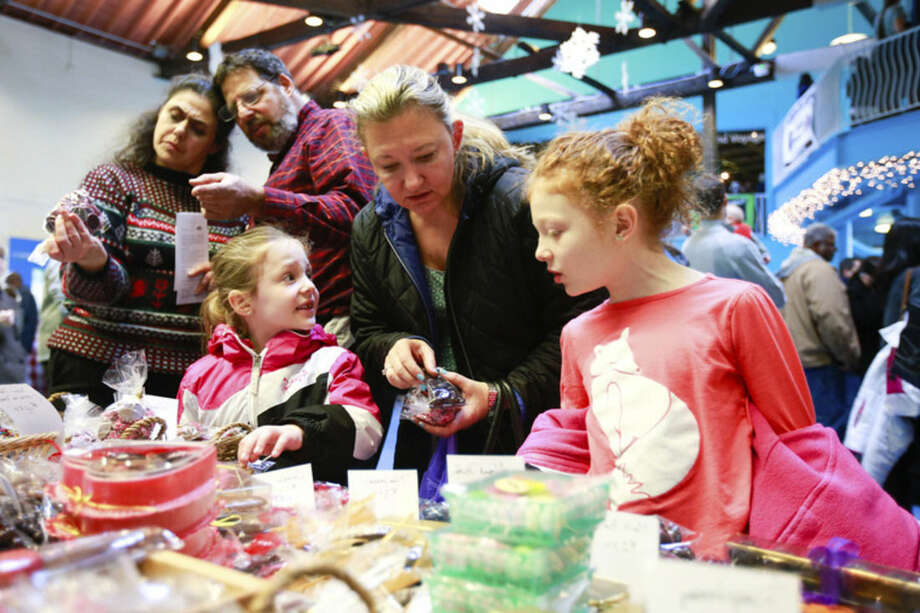 Hour photo/Chris Palermo Matilda, Lynn and Jacobi Odin purchase chocolate at the annual Chocolate Expo at the Maritime Aquarium in Norwalk Sunday.