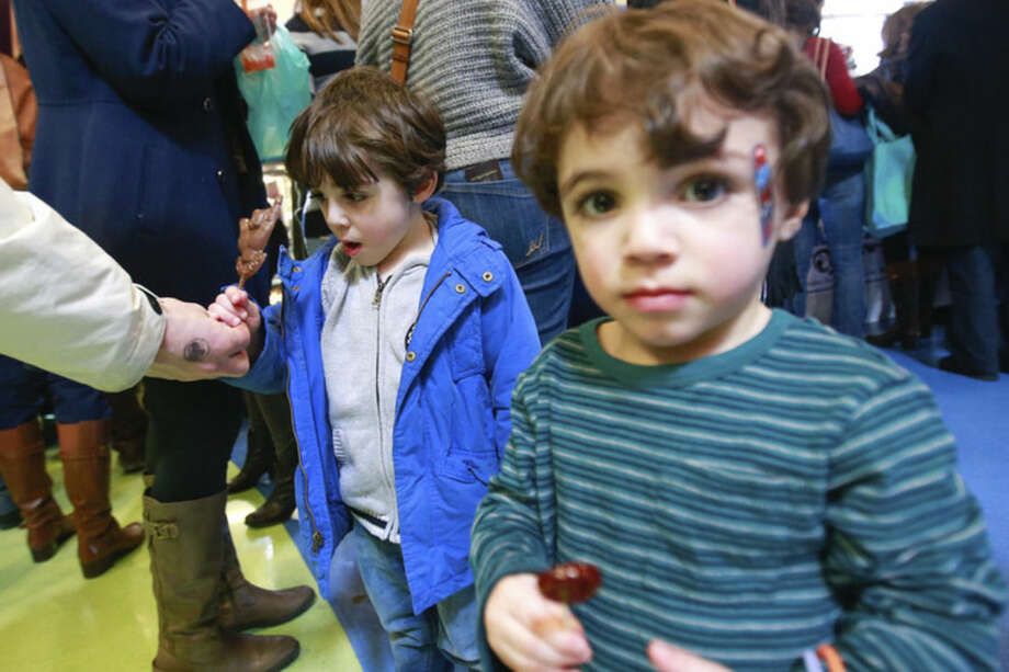 Hour photo/Chris Palermo 3-year-old Lucas Walsh, left, is surprised by a chocolate lolipop as brother Noah, 2, enjoys his own at the annual Chocolate Expo at the Maritime Aquarium in Norwalk Sunday.