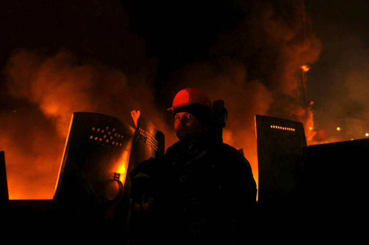 An anti-government protester mans a barricade at Independence Square in Kiev, Ukraine, Thursday, Feb. 20, 2014. Ukraine's protest leaders and the president they aim to oust called a truce Wednesday, just hours after the military raised fears of a widespread crackdown with a vow to defeat
