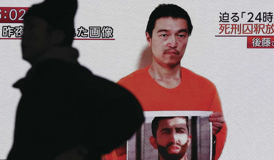 AP photo/Eugene HoshikoIn this Jan. 28, 2015 photo, a man walks by a screen showing TV news reports of a YouTube posted by a militant group on Jan. 27, purportedly showing a still photo of Japanese hostage Kenji Goto holding what appears to be a photo of Jordanian pilot Lt. Muath al-Kaseasbeh, in Tokyo.