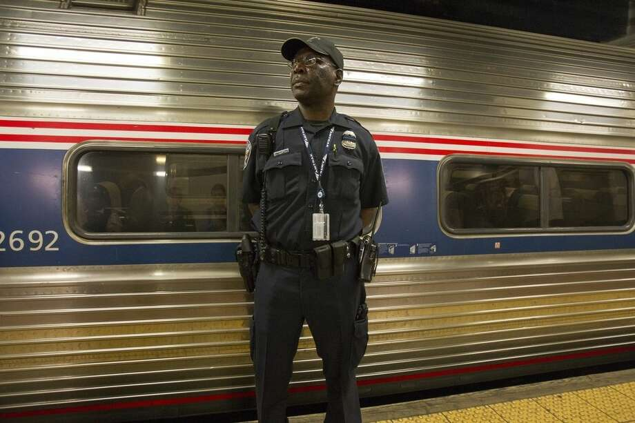 An Amtrak police officer stands guard outside Train 110, Monday, May 18, 2015, at Philadelphia's 30th Street Station. The train bound for New York's Penn Station was the first northbound train from the city since a May 12 derailment killed 8 people and injured dozens. (AP Photo/Michael R. Sisak)