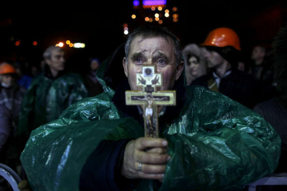 """An anti-government protester holds a crucifix as he prays at Independence Square in Kiev, Ukraine, Thursday, Feb. 20, 2014. Ukraine's protest leaders and the president they aim to oust called a truce Wednesday, just hours after the military raised fears of a widespread crackdown with a vow to defeat """"terrorists"""" responsible for seizing weapons and burning down buildings. (AP Photo/ Marko Drobnjakovic)"""