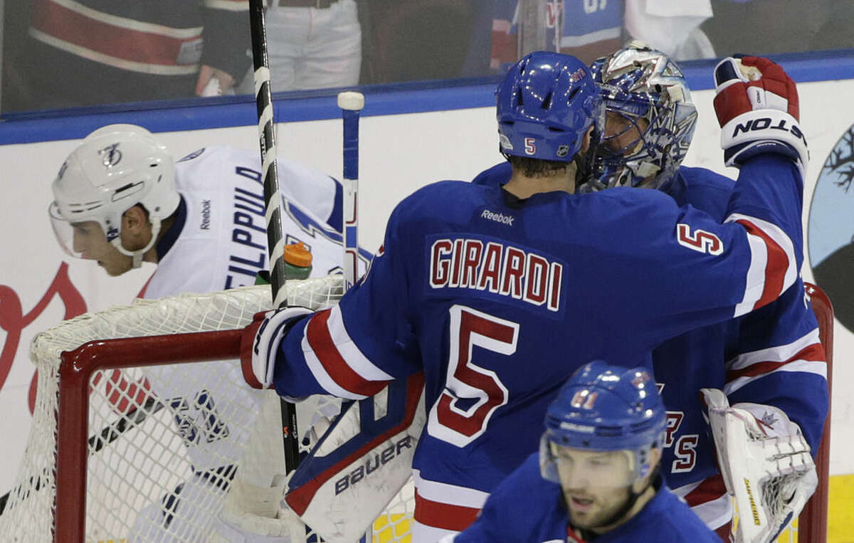 New York Rangers defenseman Dan Girardi (5) congratulates goalie Henrik Lundqvist (30) after the Rangers defeated the Tampa Bay Lightning 2-1 in Game 1 of the Eastern Conference final during the NHL hockey Stanley Cup playoffs, Saturday, May 16, 2015, in New York. The Rangers won 2-1. (AP Photo/Frank Franklin II)