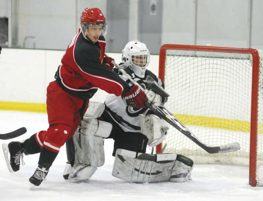Hour photo/John NashConnecticut Oilers goalie Josh Sarlo, right, and New York Apple Core forward Lukas Znosko, who hails from Stamford, make contact as a puck is tipped wide during Friday afternoon's game EHL game at the SoNo Ice House.
