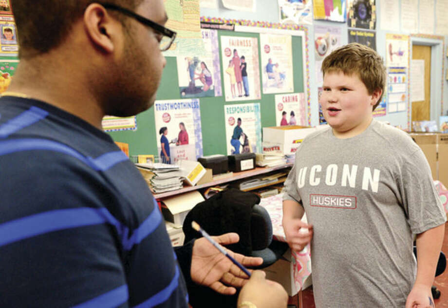 Hour photo / Erik Trautmann 5th grader Matthew Corbin talks with Sacred Heart University junior Kevin Devissiere as Fox Run Elementary School holds a College T-Shirt Day Friday, where students wear college t-shirts, research the school on their shirt and hear from college students in an effort to introduce higher education to 5th graders.