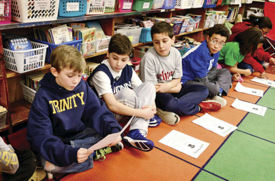 Hour photo / Erik Trautmann 5th grader Thomas Bovi reads his report on Trinity College as Fox Run Elementary School holds a College T-Shirt Day Friday, where students wear college t-shirts, research the school on their shirt and hear from college students in an effort to introduce higher education to 5th graders.