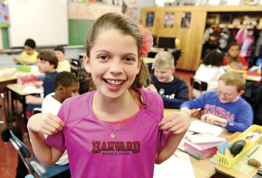 Hour photo / Erik Trautmann 5th grader Lilly Chesler shows off her Harvard Business School t-shirt, where her father is enrolled, as Fox Run Elementary School holds a College T-Shirt Day Friday, where students wear college t-shirts, research the school on their shirt and hear from college students in an effort to introduce higher education to 5th graders.