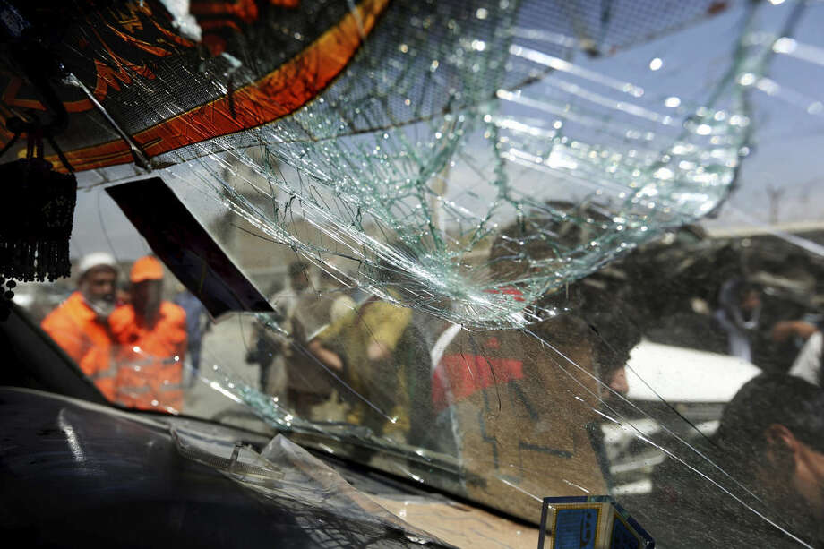 Afghan men are seen through the shattered window of a damaged car at the site of suicide bomber attack near Kabul's international airport in Afghanistan, Sunday, May 17, 2015. A suicide bomber detonated an explosives-packed car near Kabul's international airport on Sunday, wounding at least 16 civilians in an attack that may have been aimed at vehicles of the European Union Police Mission in Afghanistan, officials said. (AP Photo/Rahmat Gul)