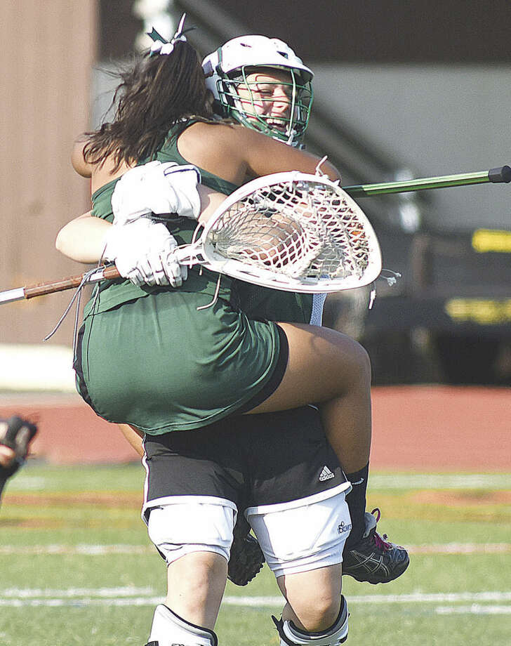 Hour photo/John NashNorwalk High junior girls lacrosse goalie Maria Bellos, rear, embraces defender and teammate Sarah Meza after the final buzzer of Tuesday's 14-11 win over Stamford put the Bears into th 2015 Class L state tournament.