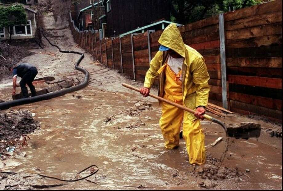 HOLD FOR RELEASE FOR 9:01 A.M. EST THURSDAY, MARCH 6, 2014 - FILE - In this Wednesday, March 25, 1998 file photo, Enrique Lagunas digs a trench to redirect water toward a street in Laguna Beach, Calif. after heavy rains from an El Nino storm hit Southern California. On Thursday, March 6, 2014, the U.S. National Oceanic Atmospheric and Administration announced their prediction of an El Nino warming of the central Pacific Ocean in 2014 that will change weather worldwide. It is expected to trigger fewer Atlantic hurricanes, more rain next winter for drought-struck California and southern states and even cause a milder winter for the nation's cold-struck northern tier next year, meteorologists say. For the world it can mean an even hotter year coming up and food crop losses. (AP Photo/Orange County Register, Bruce Chambers)