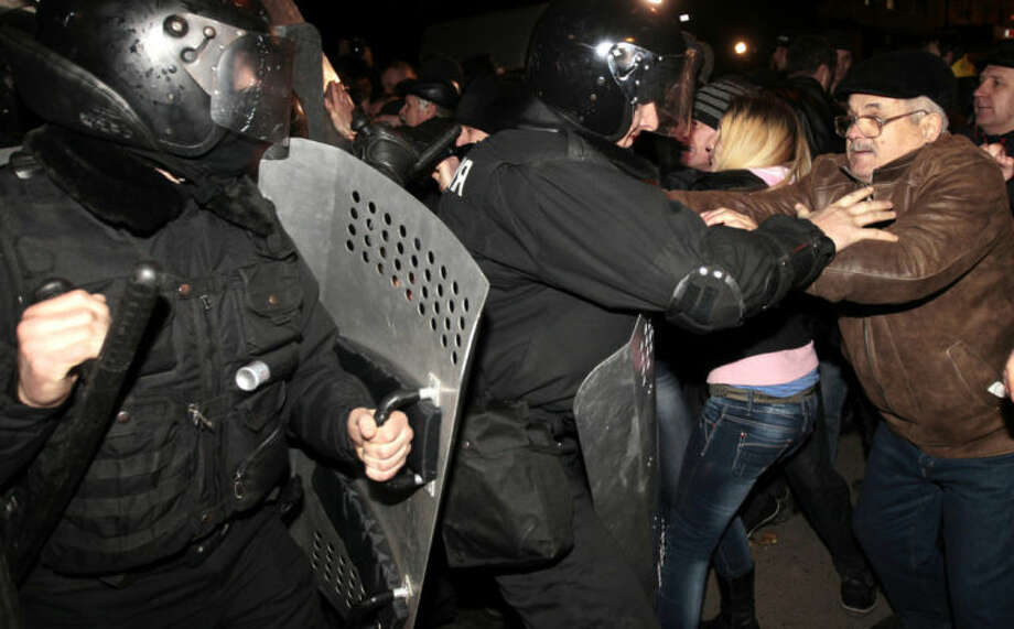 Ukrainian riot police officers block pro-Russian supporters of activist Pavel Gubarev during a rally in Donetsk, Ukraine, Thursday, March 6, 2014. Ukraine lurched toward breakup Thursday when lawmakers in Crimea unanimously declared they wanted to join Russia and would put the decision to voters in 10 days — and Russian lawmakers pushed a bill to facilitate a handover. (AP Photo/Sergei Chuzavkov)