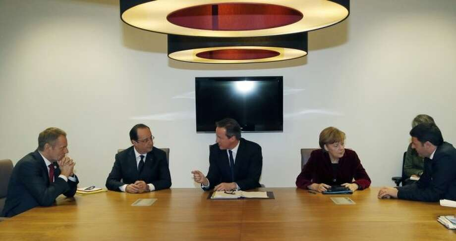 From left, Polish Prime Minister Donald Tusk, French President Francois Hollande, British Prime Minister David Cameron, German Chancellor Angela Merkel and Italian Prime Minister Matteo Renzi speak with each other during a meeting at an EU summit in Brussels on Thursday, March 6, 2014. EU heads of state meet Thursday in emergency session to discuss the situation in Ukraine. (AP Photo/Michel Euler, Pool)