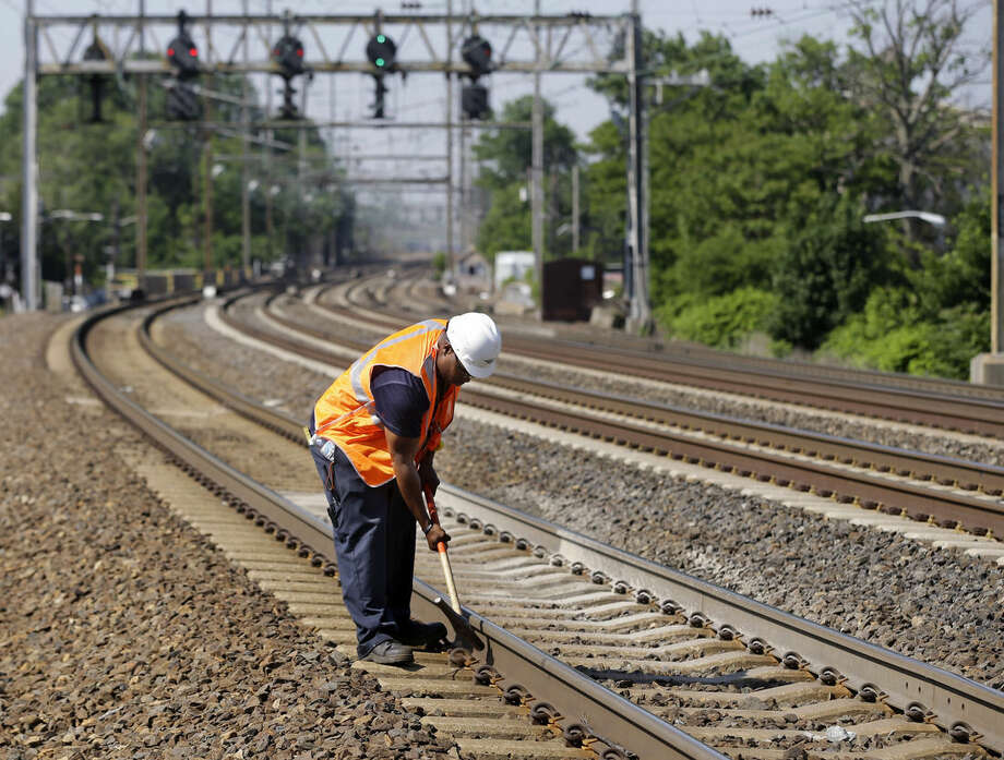 FILE - In this Thursday, May 30, 2013 file photo, Amtrak worker Rich Woolfolk checks railroad tracks along the Northeast Corridor in Elizabeth, N.J. as temperatures were expected to increase to the 90s over the next few days. Amtrak's ridership on the corridor is up 50 percent since 1998, thanks mostly to the introduction of high-speed trains now favored by travelers who used to fly between New York, Washington and Boston. Amtrak carried a record 11.6 million riders on the corridor in fiscal year 2014. (AP Photo/Mel Evans)