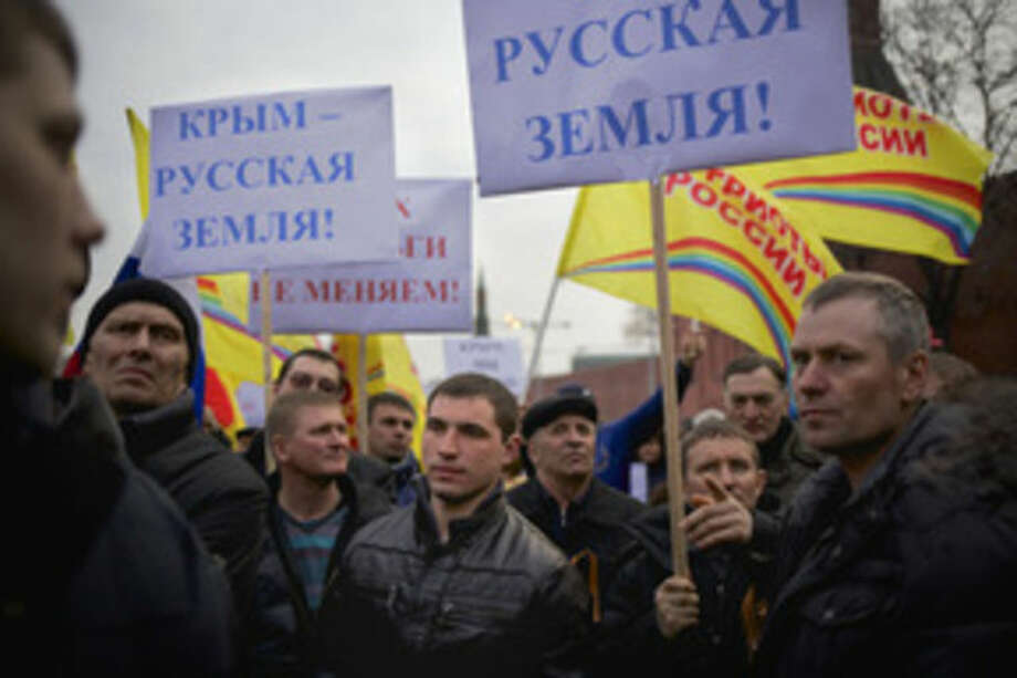 "AP photo / Alexander ZemlianichenkoPro-Putin demonstrators hold posters reading ""Crimea is Russian land!"" as they gather towards to Red Square in Moscow Friday. Russia rallied support Friday for a Crimean bid to secede from Ukraine, with a leader of Russia's parliament assuring her Crimean counterpart that the region would be welcomed as an absolutely equal subject of the Russian Federation. Across Red Square, 65,000 people waved Russian flags, chanting ""Crimea is Russia!"""