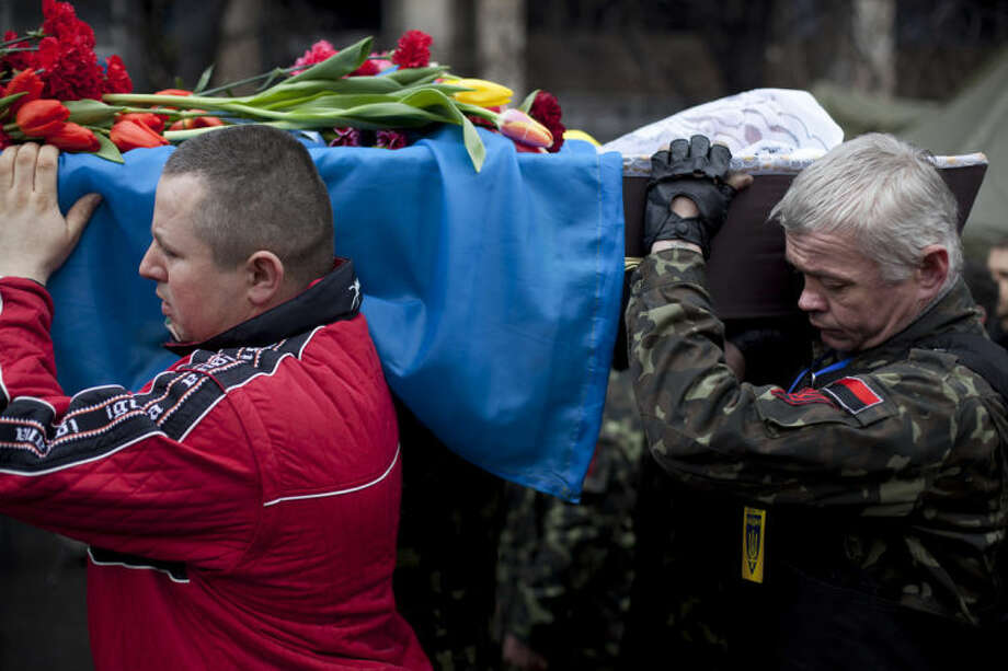 Pallbearers carry a coffin bearing the body of Andryi Pozniak, 25, a self defense volunteer who was shot and killed by an unknown assailant two days ago near Kiev's Independence Square, Ukraine, Thursday, March 6, 2014. (AP Photo/David Azia)