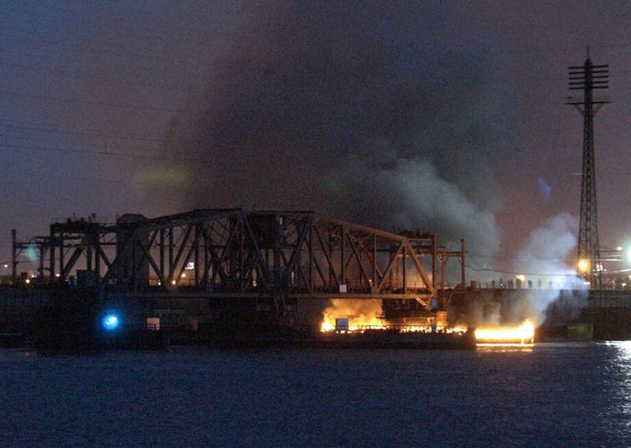 FILE - In this Thursday, May 12, 2005 file photo, fires burn at the Amtrak portal drawbridge over the Hackensack River between Secaucus and Kearny, N.J. A fast-moving fire engulfed the railroad bridge in northern New Jersey, disrupting New Jersey Transit and Amtrak service on the Northeast Corridor. (AP Photo/Bill Kostroun)