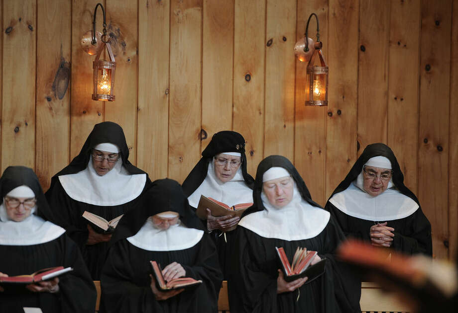 """In this Friday, May 15, 2015 photo, Mother Dolores Hart, top center, attends a Vespers, evening prayer, at the Abbey of Regina Laudis, in Bethlehem, Conn. Mother Dolores, a former actress who is best known for sharing the first on-screen kiss with Elvis Presley in the 1957 film """"Loving You"""", has helped the Abbey which is in need of renovations gain exposure and aid from fans of Presley. (AP Photo/Jessica Hill)"""