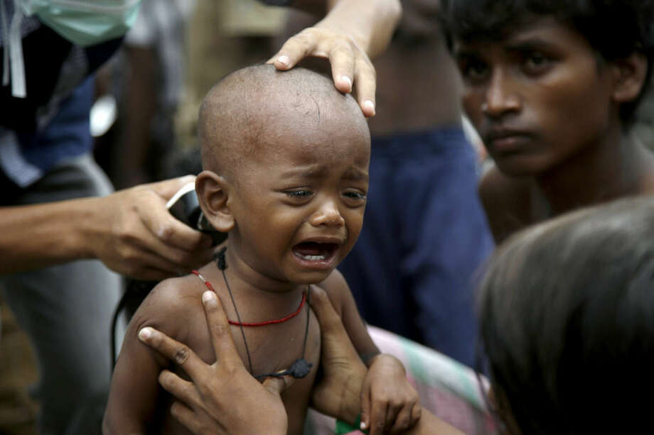 An ethnic Rohingya kid cries after receiving a free haircut service provided by a local charity at a temporary shelter in Langsa, Aceh province, Indonesia, Friday, May 22, 2015. Thousands of refugees and migrants have washed ashore in Malaysia, Indonesia and Thailand, about half Rohingya and the rest from Bangladesh, according to the International Organization for Migration. The U.N. refugee agency estimates more than 3,000 others may still be at sea.(AP Photo/Tatan Syuflana)