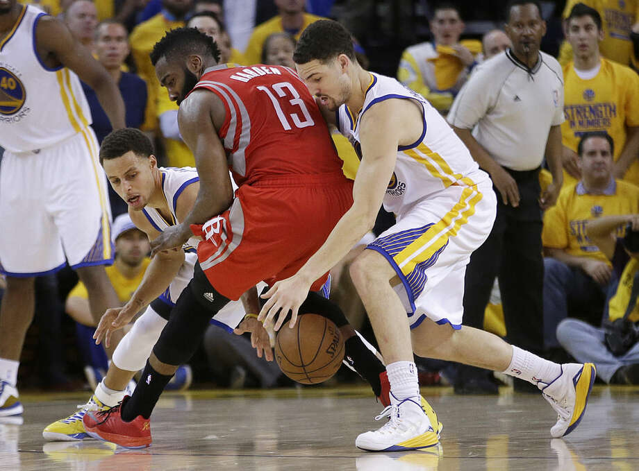 Houston Rockets guard James Harden (13) loses the ball on the game's final play as Golden State Warriors guards Stephen Curry, left, and Klay Thompson defend during the second half of Game 2 of the NBA basketball Western Conference finals in Oakland, Calif., Thursday, May 21, 2015. The Warriors won 99-98. (AP Photo/Rick Bowmer)