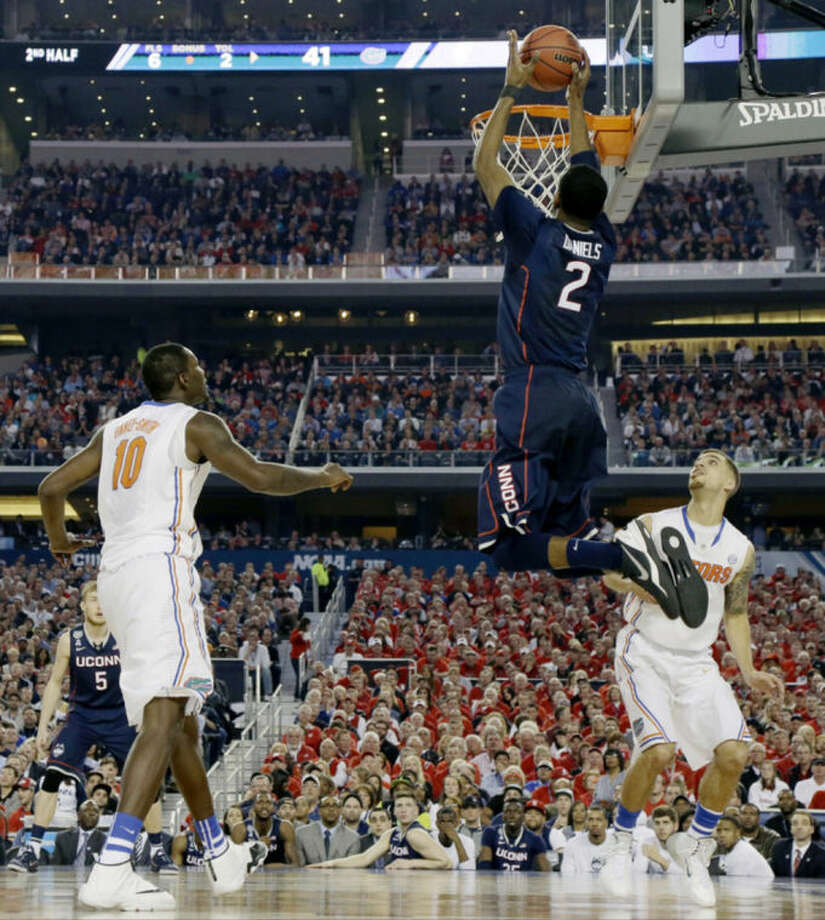 Connecticut forward DeAndre Daniels (2) shoots between Florida forward Dorian Finney-Smith (10) and guard Scottie Wilbekin (5) during the second half of the NCAA Final Four tournament college basketball semifinal game Saturday, April 5, 2014, in Arlington, Texas. (AP Photo/Eric Gay)