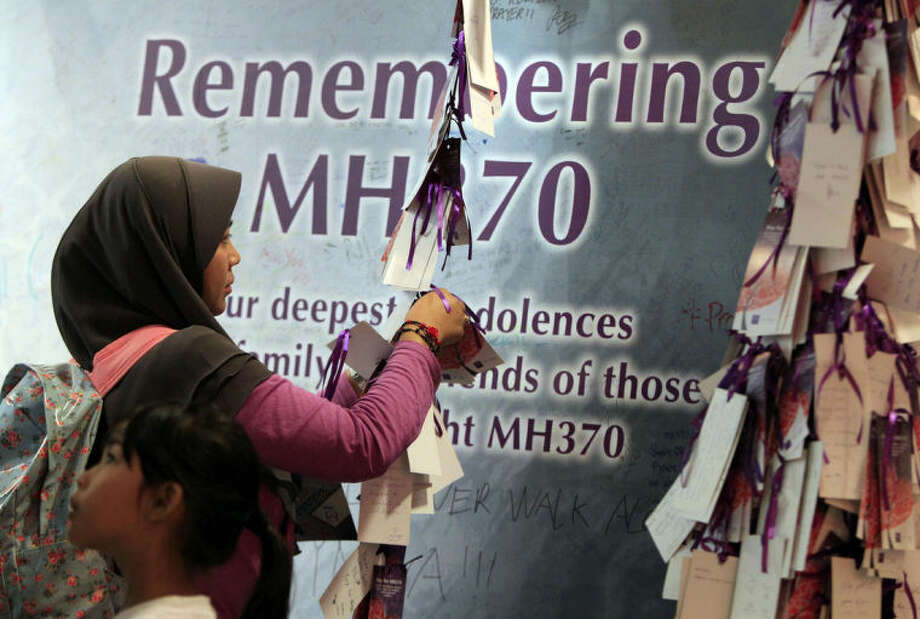 A woman ties a message card for passengers aboard the missing Malaysia Airlines flight MH370, at a shopping mall in Kuala Lumpur, Malaysia, Saturday, April 5, 2014. Search teams racing against time to find the flight recorders from the missing Malaysia Airlines jet crisscrossed another patch of the Indian Ocean on Saturday, four weeks to the day after the airliner vanished. (AP Photo/Lai Seng Sin)
