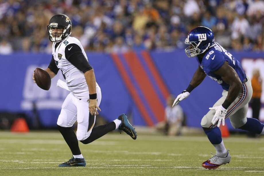 Jacksonville Jaguars quarterback Blake Bortles (5) runs away from New York Giants defensive end Owamagbe Odighizuwa (58) during the first half of a preseason NFL football game Saturday, Aug. 22, 2015, in East Rutherford, N.J. (AP Photo/Adam Hunger)