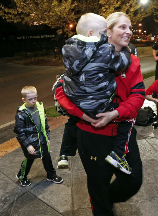 Maryland coach Brenda Frese carries one of her twin sons, Tyler, 6, as his brother, Markus, left, follows as the team arrives for the NCAA women's Final Four college basketball tournament Thursday, April 3, 2014, in Nashville, Tenn. Maryland is scheduled to play Notre Dame in a semifinal on Sunday. (AP Photo/Mark Humphrey)
