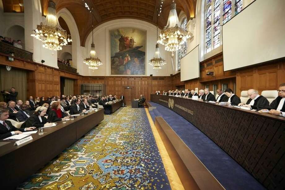 Representatives of Australia and Japan wait for the International Court of Justice to deliver its verdict in The Hague, Netherlands, Monday March 31, 2014. The International Court of Justice is ruling Monday on Australia's challenge against Japan for whaling in Antarctic waters. (AP Photo/Phil Nijhuis)