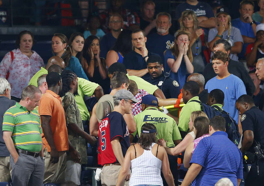 Rescue workers carry an injured fan from the stands at Turner Field during a baseball game between Atlanta Braves and New York Yankees Saturday, Aug. 29, 2015, in Atlanta. (AP Photo/John Bazemore)