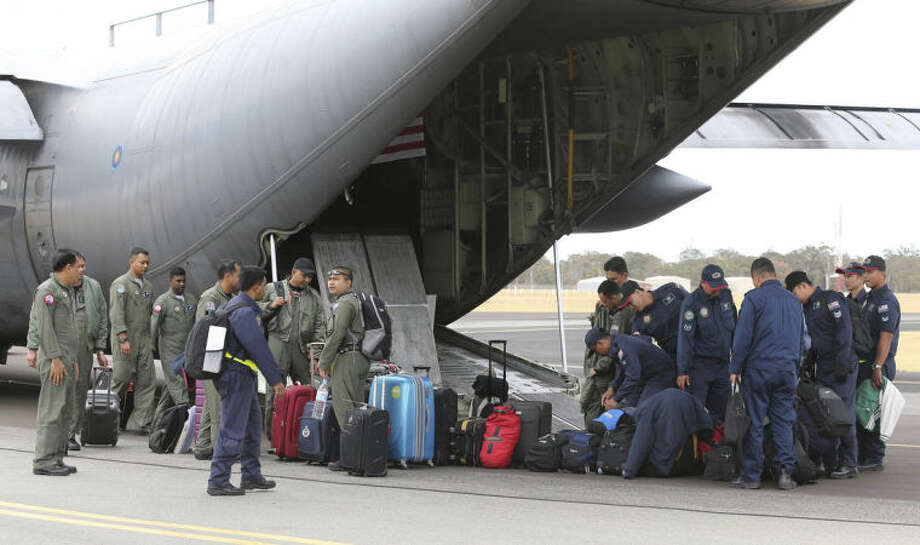 Crew onboard a Royal Malaysian Air Force C-130 Hercules unloads the aircraft after it landed at RAAF Base Pearce to to help with the search for debris or wreckage of the missing Malaysia Airlines Flight MH370 in Perth, Australia, Saturday, March 29, 2014.(AP Photo/Rob Griffith, Pool)