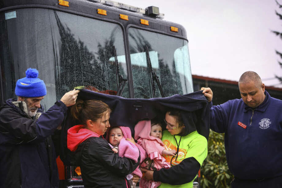 Volunteer Ralph Jones, left, and Tim Perciful of the Mountainview, Black Diamond Fire Department, help keep Klarissa Calviste and her daughter Kielie Braaten, left, and Brooke Odenius and her daughter Bexli dry as they observe a state-wide moment of silence to honor the victims of the Oso mud slide in front of the Darrington, Wash. Fire Department on Saturday, March 29, 2014. Gov. Jay Inslee had asked people across Washington to pause at 10:37 a.m. The huge slide that destroyed a neighborhood in Oso north of Seattle struck at that time on March 22. Authorities say they've found at least 25 bodies and scores remain missing. (AP Photo/seattlepi.com, Joshua Trujillo)