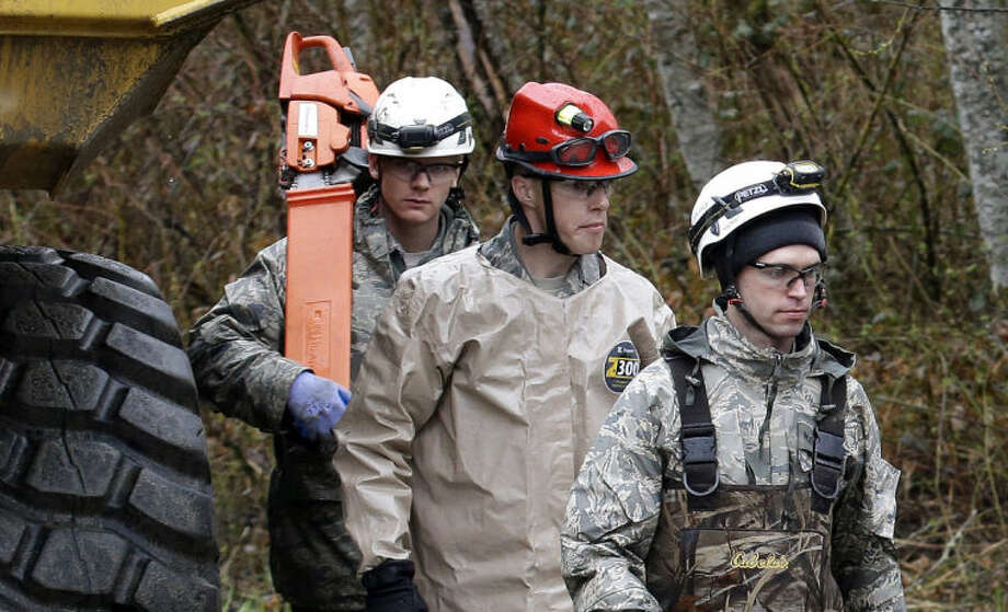 Searchers walk past heavy equipment as they leave the scene of a deadly mudslide, Saturday, March 29, 2014, in Oso, Wash. Besides the more than two dozen bodies already found, many more people could be buried in the debris pile left from the mudslide one week ago. Ninety people are listed as missing. (AP Photo/Elaine Thompson, Pool)