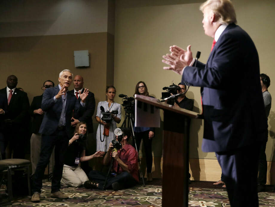 Miami-based Univision anchor Jorge Ramos, left, asks Republican presidential candidate Donald Trump a question about his immigration proposal during a news conference, Tuesday, Aug. 25, 2015, in Dubuque, Iowa. Ramos was later taken from the room. (AP Photo/Charlie Neibergall)