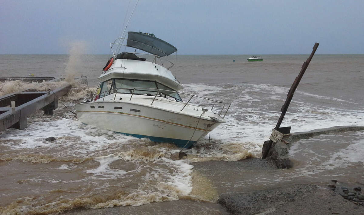 A boat sits in shallow water as Tropical Storm Erika passes through New Town, Dominica, Thursday, Aug. 27, 2015. Erika was expected to move near Puerto Rico and the Virgin Islands on Thursday and be near or just north of the Dominican Republic on Friday as it heads toward Florida early next week, possibly as a hurricane. (AP Photo/Carlisle Jno Baptiste)