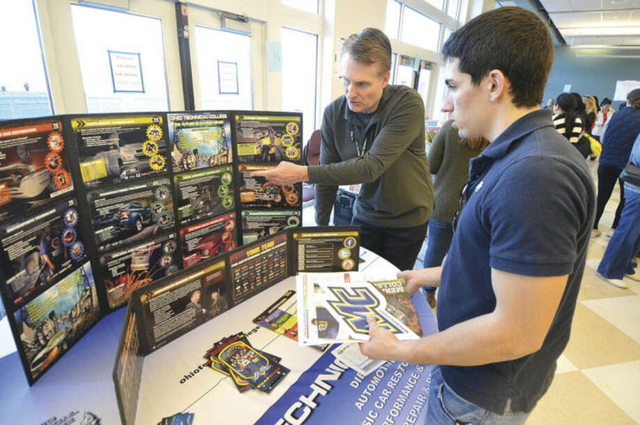 Hour Photo/Alex von KleydorffMassimo Diferico speaks with admissions representative Ron Zelman about Ohio Technical College at the Citywide College Fair at Brien McMahon High School.