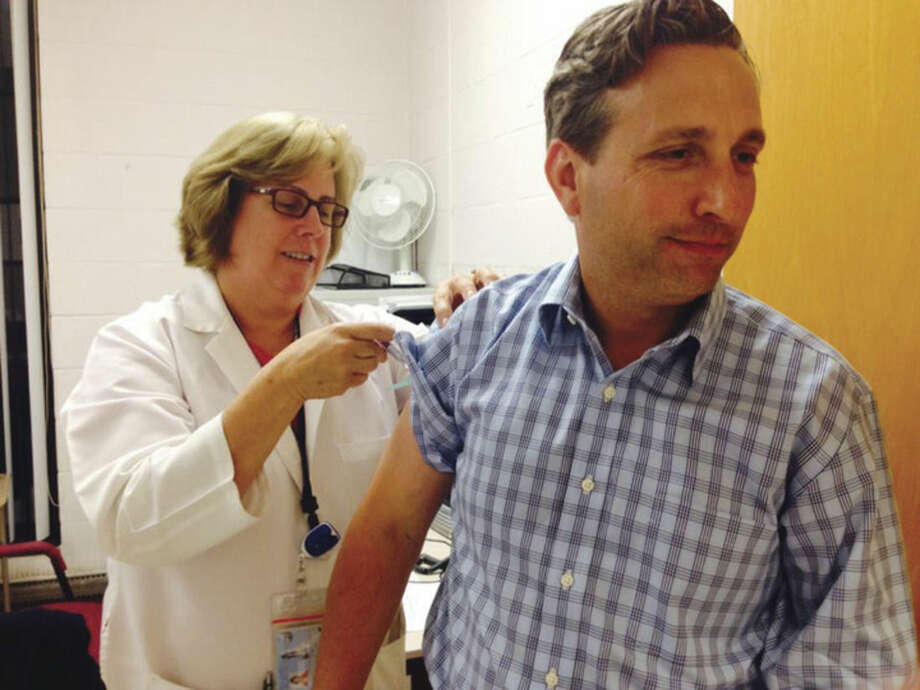 Contributed photoState Sen. Bob Duff gets his flu shot from the Health Department in September 2014 in this file photo. The nurse providing the shot is Patricia Carey, MS, APRN, Communicable Disease Program Coordinator.