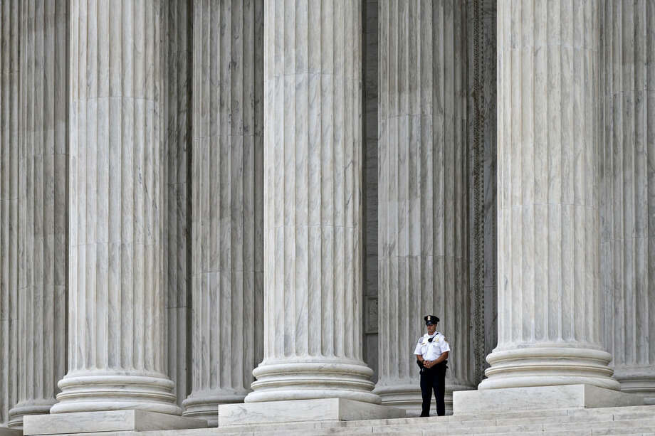 A police officer is dwarfed amid the marble columns of the Supreme Court in Washington, Tuesday, Oct. 7, 2014, as the justices heard arguments on the second day of the new term. The justices cleared the way Monday for an immediate expansion of same-sex marriage by unexpectedly and tersely turning away appeals from five states seeking to prohibit gay and lesbian unions. The court's order effectively makes gay marriage legal now in 30 states. (AP Photo/J. Scott Applewhite)