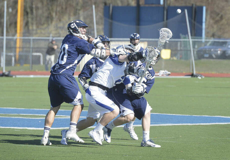 Hour photo/Alex von KleydorffDarien's William Hammernick is mobbed by Wilton defenders during Thursday's game. Darien won 17-6.