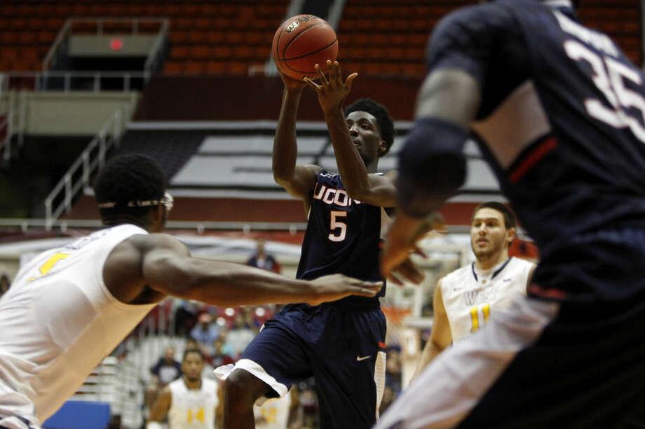 UConn guard Daniel Hamilton, center, goes to the basket against West Virginia forward Devin Williams, left, during a NCAA college basketball game in San Juan, Puerto Rico, Sunday, Nov. 23, 2014. (AP Photo/Ricardo Arduengo)