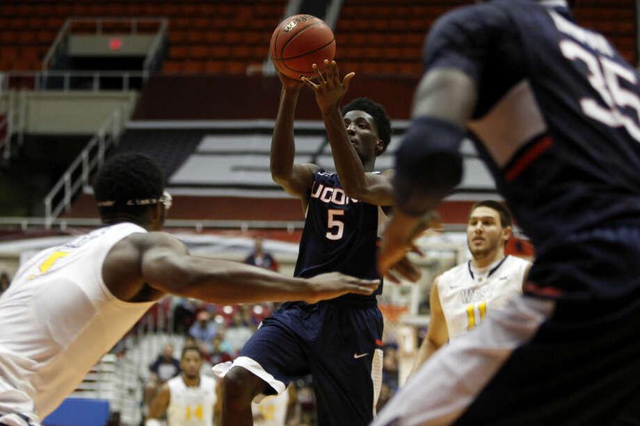 UConn guard Daniel Hamilton, center, goes to the basket against West Virginia forward Devin Williams, left, during a NCAA college basketball game in San Juan, Puerto Rico, Sunday, Nov. 23, 2014. (AP Photo/Ricardo Arduengo)