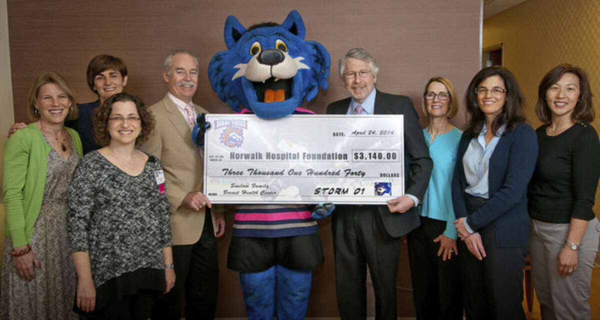 The Bridgeport Sound Tigers team mascot, Storm, presents Norwalk Hospital with a $3,140 check raised from the ?'Pink Rink Night?