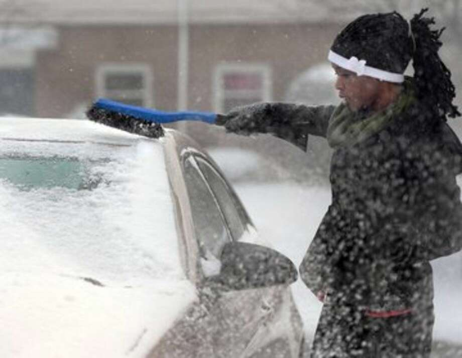 Pamela Oduho, 26, cleans ice and snow from her car in Erie, Pa. on Monday, Jan. 5, 2015. The temperature was 21 degrees as Oduho brushed and scraped. (AP Photo/Erie Times-News, Greg Wohlford)