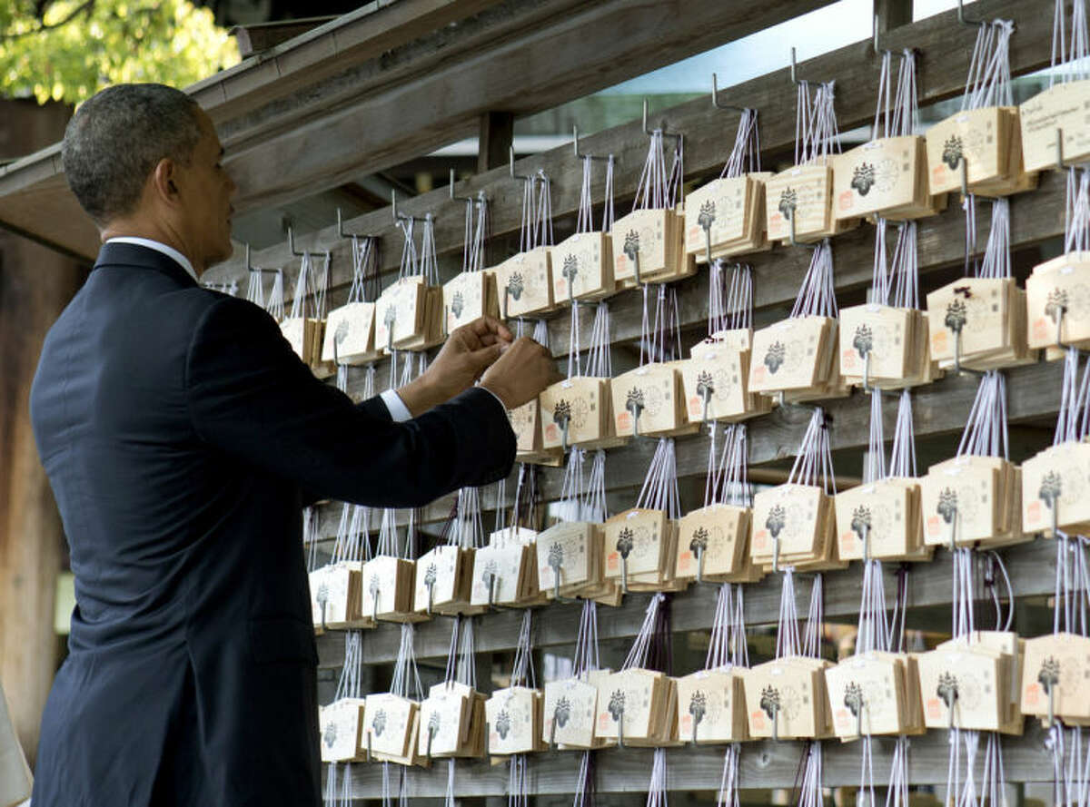 President Barack Obama places a prayer tablet on the Votive Tree as he tours Meiji Shrine in Tokyo, Thursday, April 24, 2014. Showing solidarity with Japan, Obama affirmed Thursday that the U.S. would be obligated to defend Tokyo in a confrontation with Beijing over a set of disputed islands, but urged all sides to resolve the long-running dispute peacefully. (AP Photo/Carolyn Kaster)